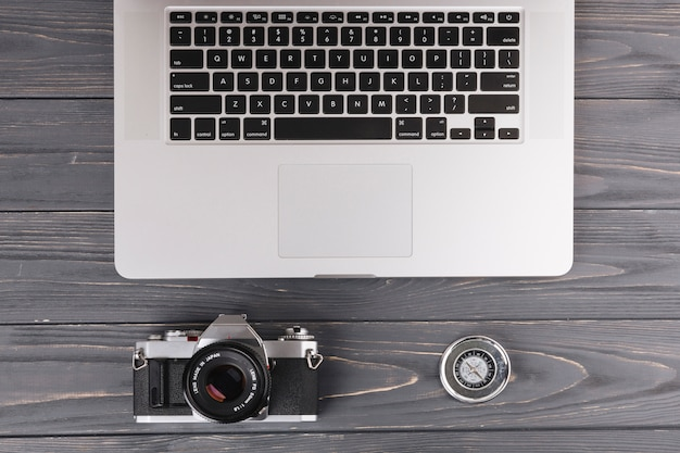 Laptop with camera and compass on wooden table