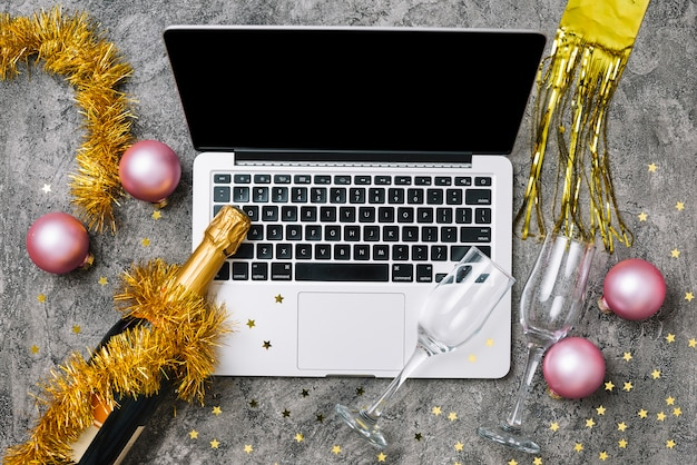 Laptop with champagne bottle on table