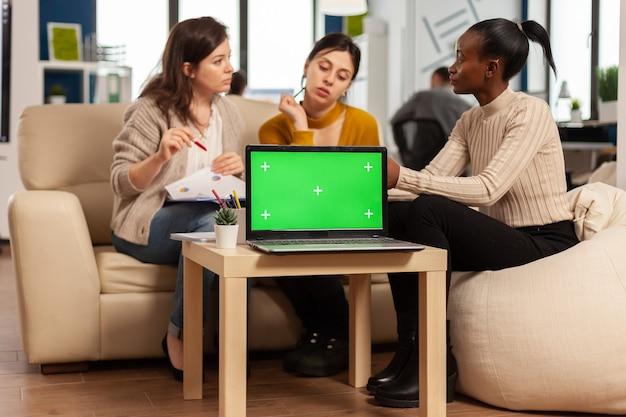 Computer portatile con display chroma key sul tavolo nel posto di lavoro aziendale di avvio
