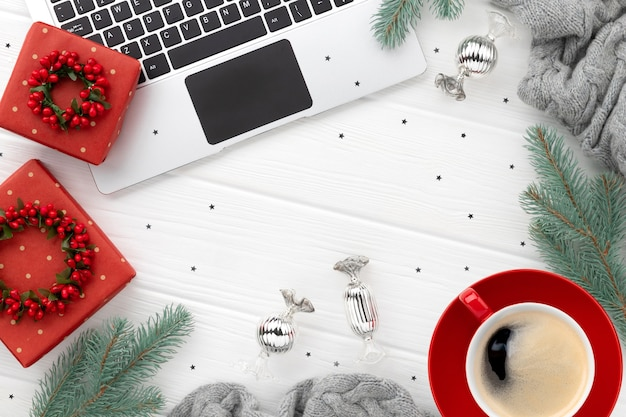 Laptop with coffee and gifts on white wood. christmas flat lay