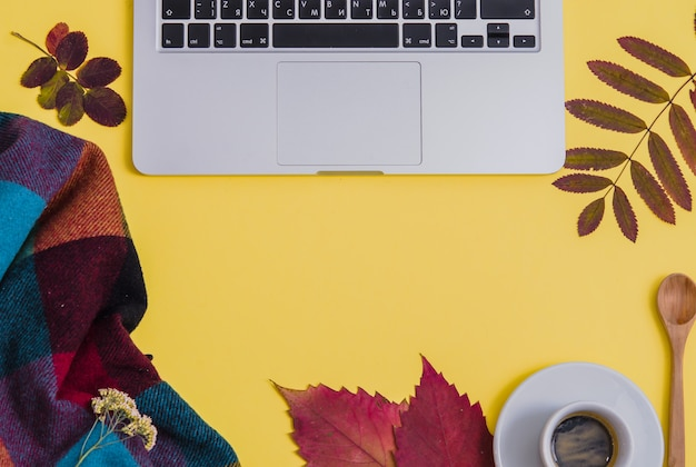 Laptop with coffee, herbarium and blanket on yellow background. autumn.