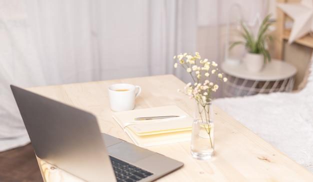 木製のテーブルにコーヒーとラップトップ