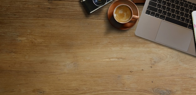 Laptop with coffee on wooden table. panoramic banner