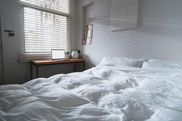 Ноутбук с копией пространства пустой экран и кровать с белыми простынями