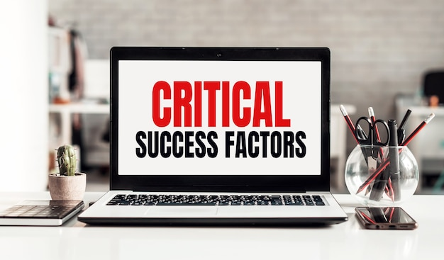 Laptop with critical success factors text on modern office surface