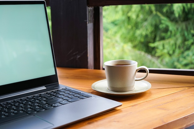 Laptop with a cup on a wooden table in the street, close up