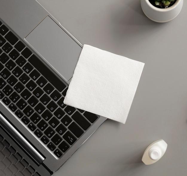 Ноутбук с дезинфицирующим средством в офисе
