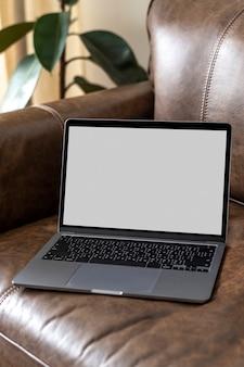 Computer portatile con schermo vuoto su un divano in pelle