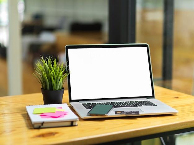 빈 화면 모니터 스마트폰 신용 카드 스티커 메모와 나무 테이블에 물건이 있는 노트북