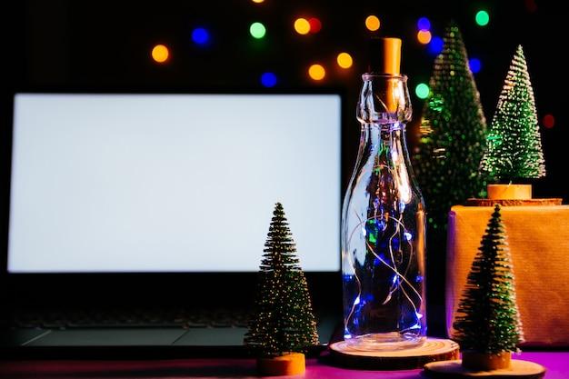 나무 테이블에 빈 화면이 있는 노트북은 배경에 크리스마스 트리와 선물을 흐리게 합니다. 크리스마스와 새 해 복 많이 받으세요 카드, bokeh, 스파크. 평평한 평지, 평면도