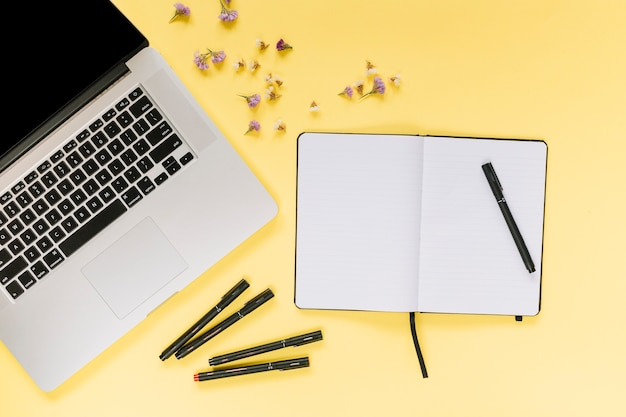 Laptop with felt-tip pens; blank notebook with lavender flowers on yellow background