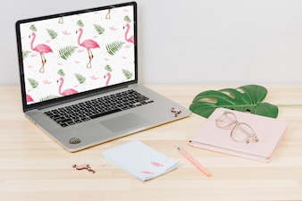 Laptop with flamingos on screen on table