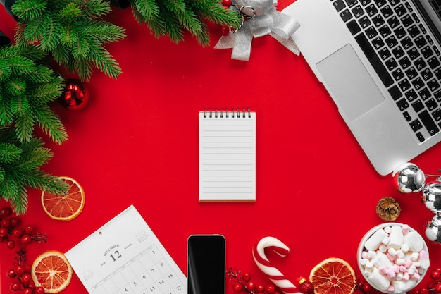 모피 나뭇 가지와 빨간색 배경 평면도에 크리스마스 훈장을 가진 노트북