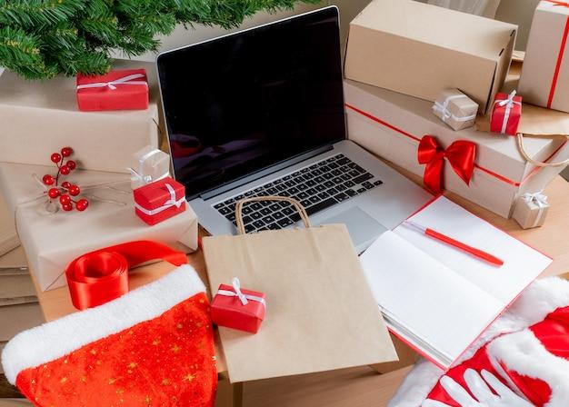 Ноутбук с подарками, упаковочные коробки и хозяйственная сумка на рабочем месте