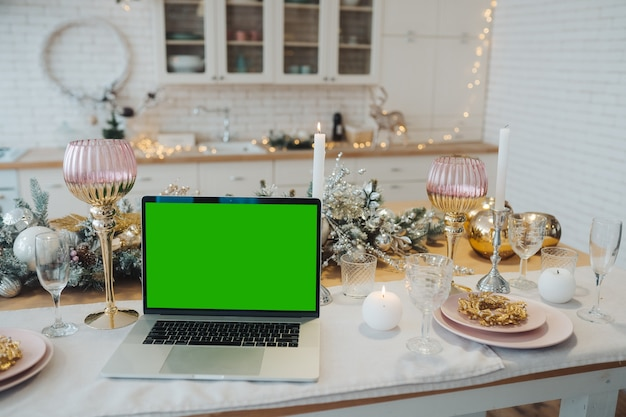 Laptop with green screen - chromakey near new year's decorations. christmas theme. template.