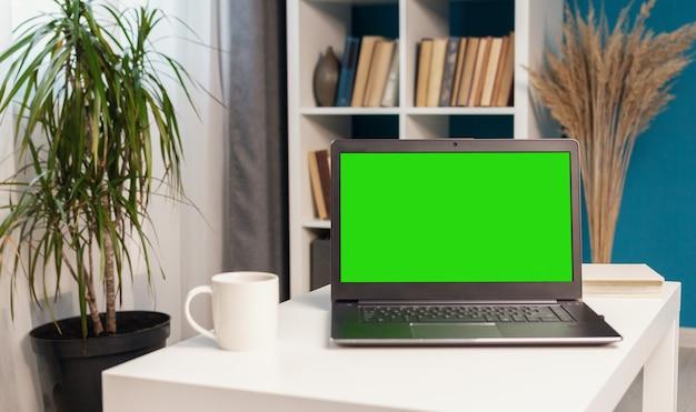 Ноутбук с зеленым экраном на столе в квартире, книжный шкаф на фоне