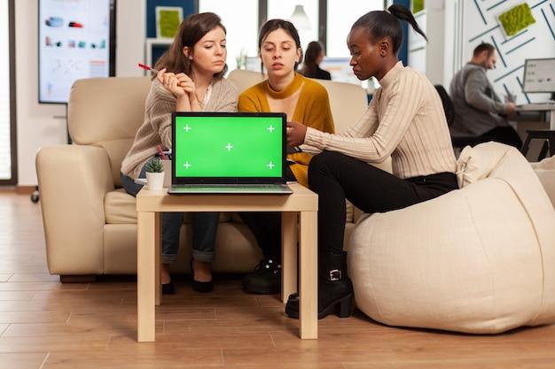 Ноутбук с зеленым экраном на столе в начинающей компании с многонациональными разноплановыми коллегами, работающими вместе за ним