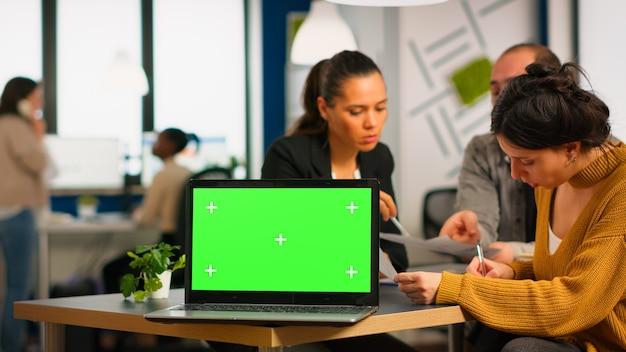 Ноутбук с зеленым экраном, готовым к презентации, помещен на стол, пока деловые люди работают в фоновом режиме. группа сотрудников, использующих ноутбук с дисплеем с цветным ключом. макет монитора