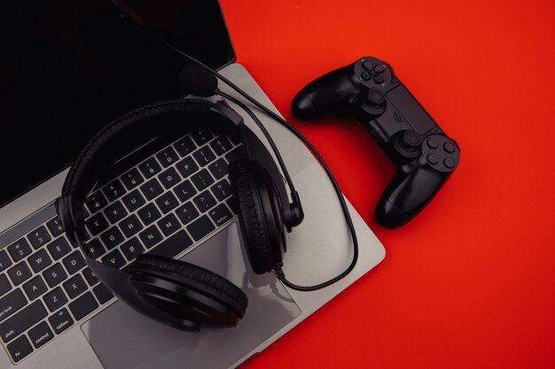 헤드폰 및 빨간색 배경에 검은 색 게임 패드와 노트북.