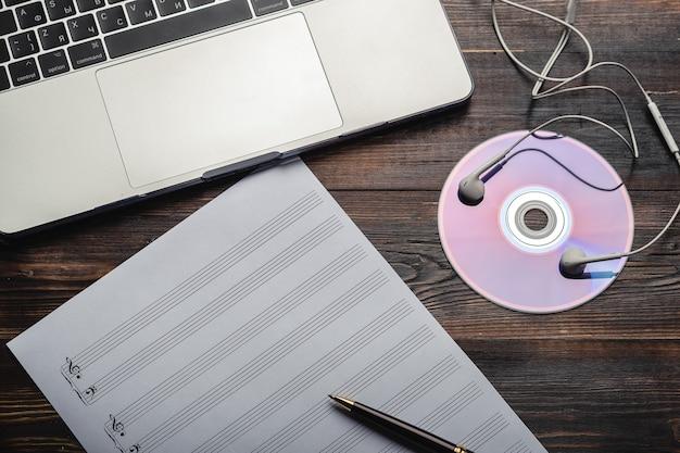 ヘッドフォン cd と音楽の紙を木製の背景にペンでノート パソコンのテキスト トップのコピー スペース