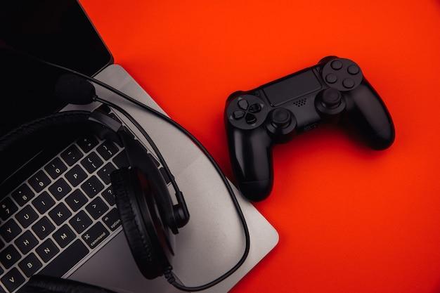 헤드폰, 빨간색 배경에 게임 패드와 노트북.