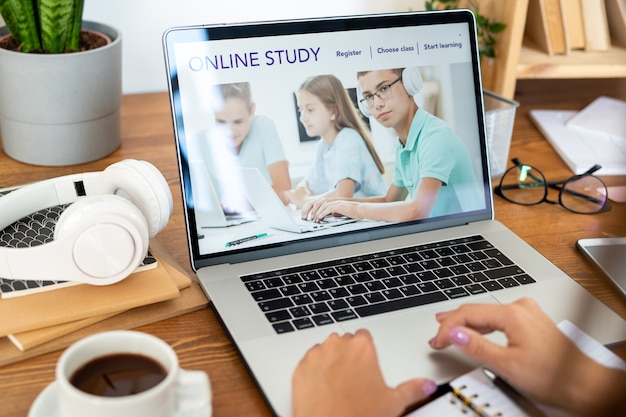 Ноутбук с домашней страницей образовательного веб-сайта на дисплее, используемый молодой студенткой за столом