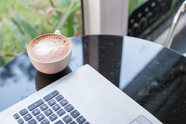 Laptop with latte hot coffee in white cup on glass table