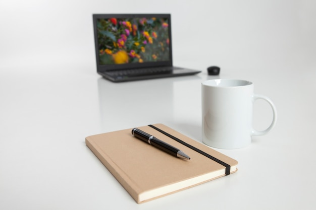 Laptop with lid open in the, notebook and cup of coffee in the foreground