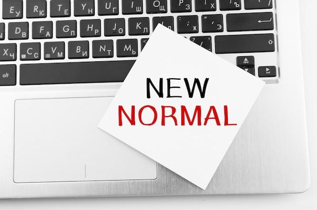 메모가있는 노트북은 키보드에 new normal이라는 텍스트가 붙어 있습니다.