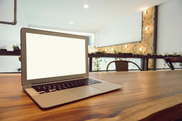 Ноутбук с макет пустой экран на деревянный стол в передней части coffeeshop кафе место для текста. концепция дисплея дисплея продукта