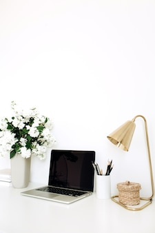 テーブルの上のモックアップ空白のコピースペース画面とラップトップ。花の花束、テーブルランプとオフィスデスクワークスペース