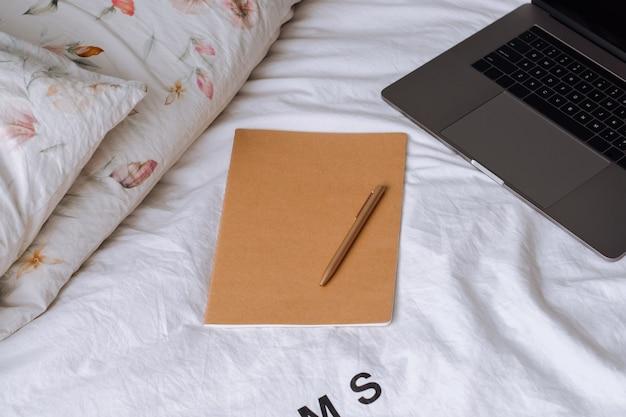 Ноутбук с блокнотом и ручкой на кровати.