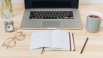 Laptop with notebook on wooden table