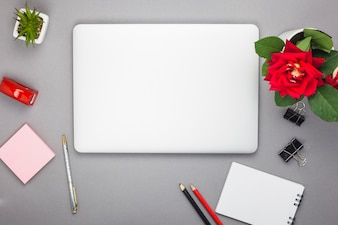 Laptop with notepad on table