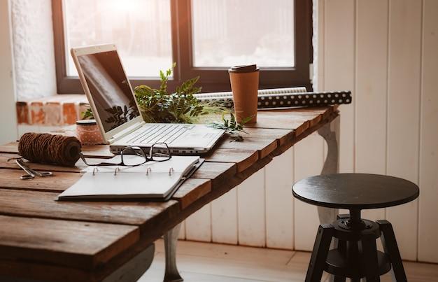 Ноутбук с канцелярскими принадлежностями и гаджетами на столе