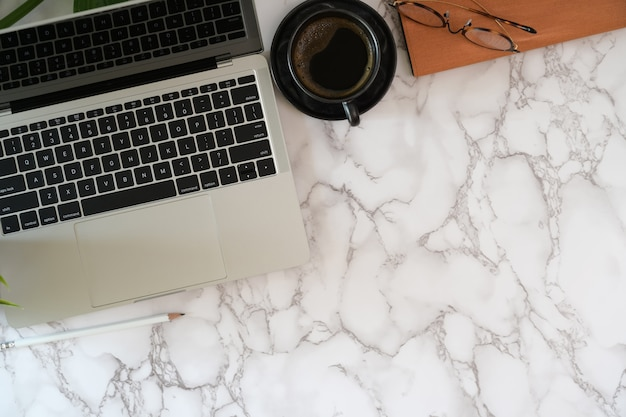 Laptop with office supplies on marble desktop