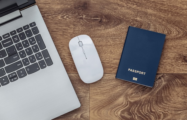Pcマウス付きノートパソコン、木の床にパスポート。上面図。ファルトレイ