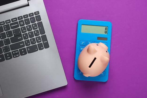 Laptop with piggy bank, calculator on purple