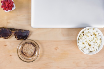 Laptop with popcorn and sunglasses on table
