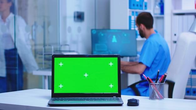 Computer portatile con schermo sostituibile nell'armadietto dell'ospedale, medico che indossa un cappotto che arriva in clinica e infermiere che scrive prescrizione. notebook con schermo verde in clinica medica.