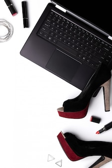 Laptop with shoes, lipstick and accessories isolated on white backgroud