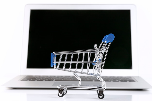 Laptop with a small shopping trolley, on a white wall. selective focus. copy space.
