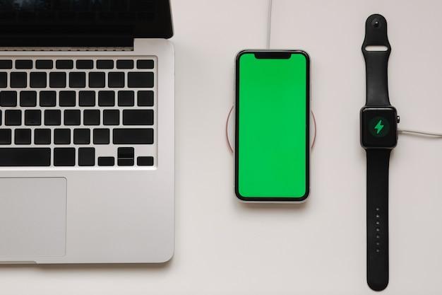 스마트 시계와 무선 충전기로 충전하는 전화가있는 노트북. 휴대 전화의 녹색 화면, 시계의 화면 충전 표시기. 평면도. 텍스트를위한 장소
