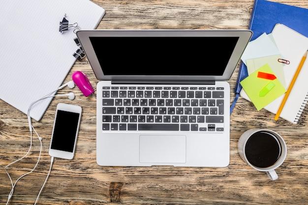 배경에 스마트폰과 커피가 있는 노트북