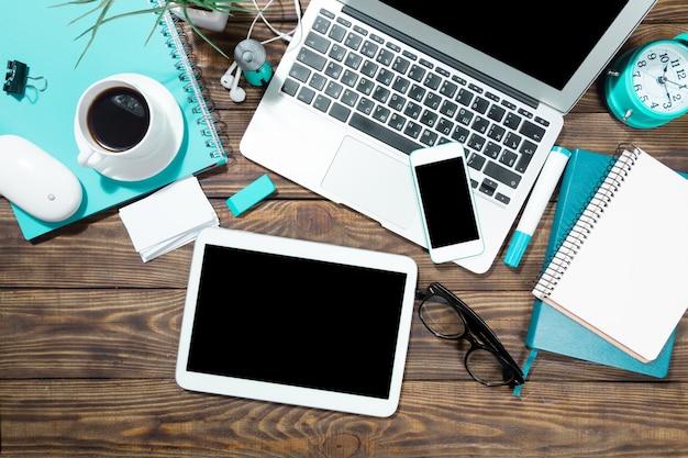 배경에 스마트폰, 커피 및 테이블 pc가 있는 노트북