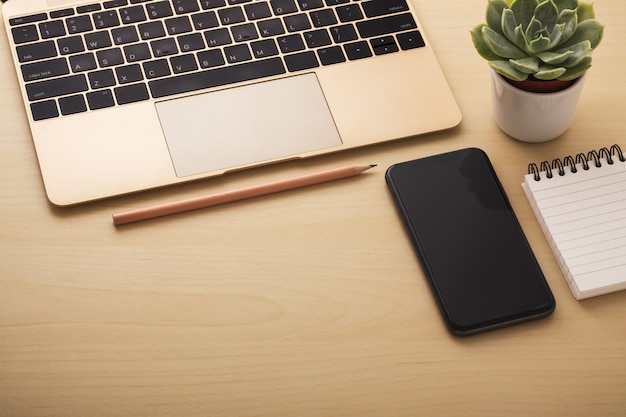 オフィスの机の上のスマートフォンとノートパソコン