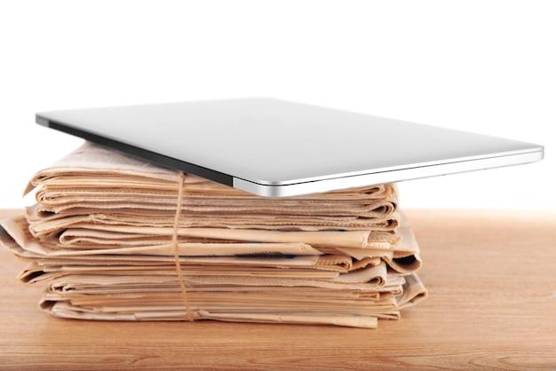 흰색 표면에 테이블에 신문의 스택과 함께 노트북