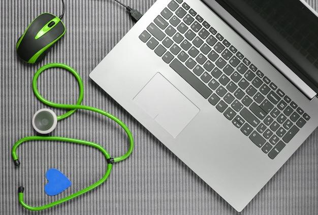 Ноутбук со стетоскопом и компьютерной мышью