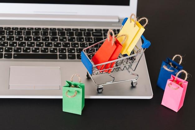 Ноутбук с игрушечной тележкой и упаковками для супермаркетов