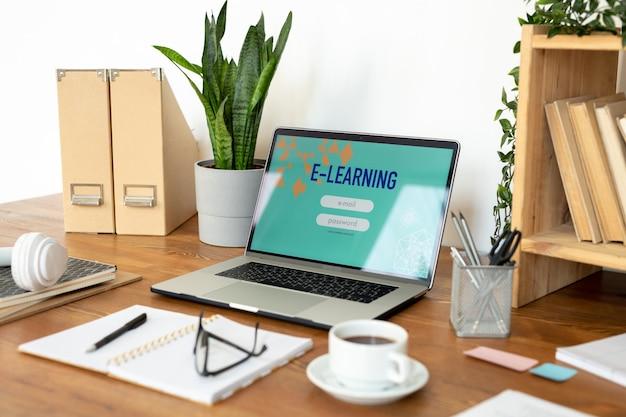 Ноутбук с домашней страницей веб-сайта на дисплее в окружении других канцелярских товаров и предметов на столе